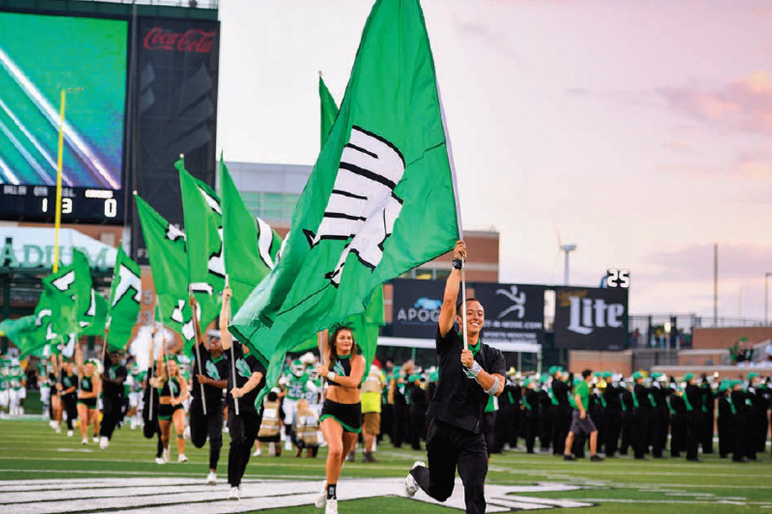 At a UNT football game, UNT students participate in spirit by running flags across the field.
